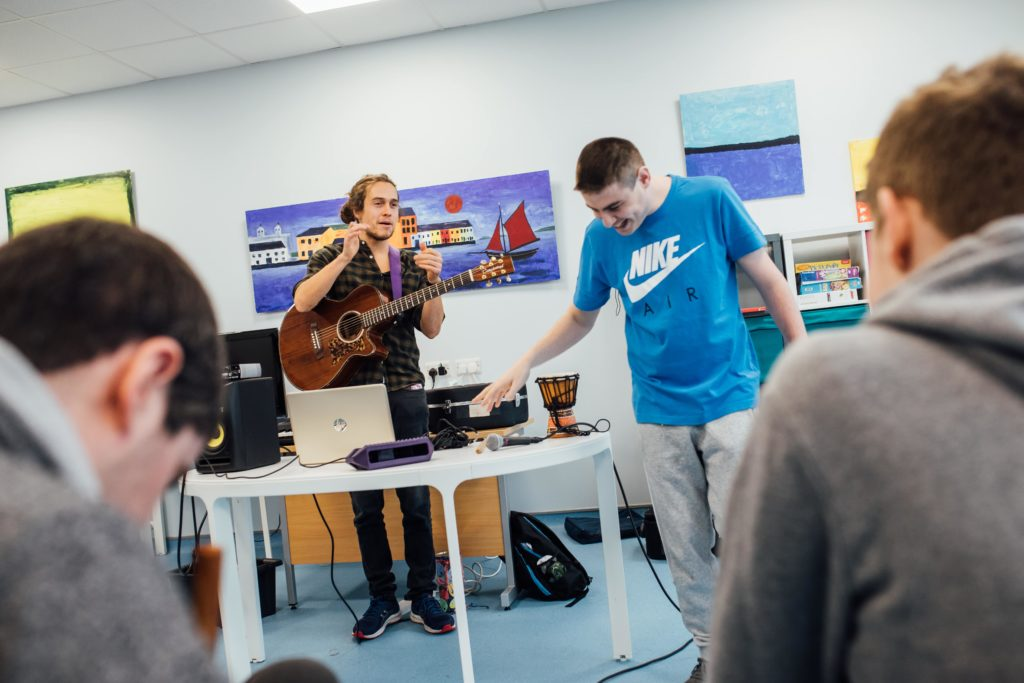 Praxis team member conducting a music session with service users